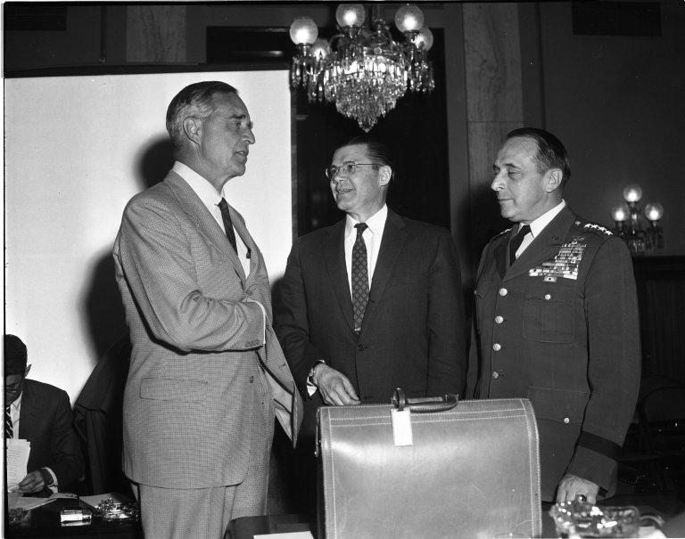 Senator Prescott S. Bush (R-CT), Secretary of Defense Robert S. McNamara and Chairman of the Joint Chiefs of Staff Lyman Lemnitzer