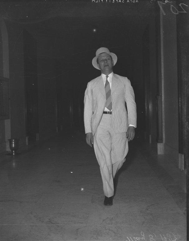 Senator Allen J. Ellender (D-LA) walking down a hallway