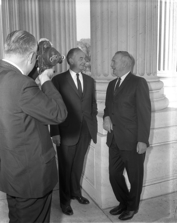 Senators Len B. Jordan (R-ID) and John J. Williams (R-DE) being photographed in front of columns, with photographer