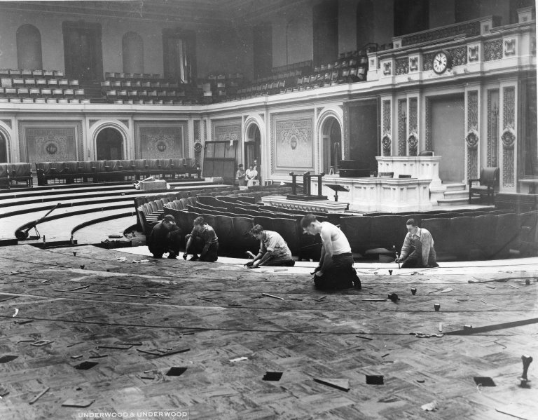 Workers lay down a new rubber flooring in the House Chamber