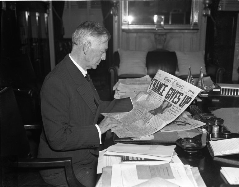 """Senator Key Pittman (D-NV) looking at a newspaper with the headline """"France Gives In"""""""