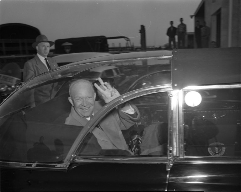 President Dwight D. Eisenhower in plastic topped car on his return from Denver, CO