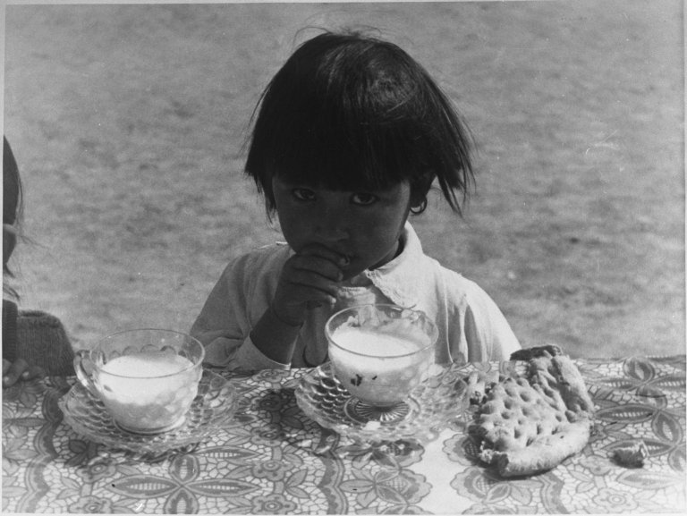 Young child sitting at table with milk and bread.