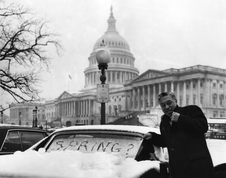 "Senator Hiram Fong (R-HI) in front of the U.S. Capitol building, next to car with ""Spring?"" written in the snow on its window"