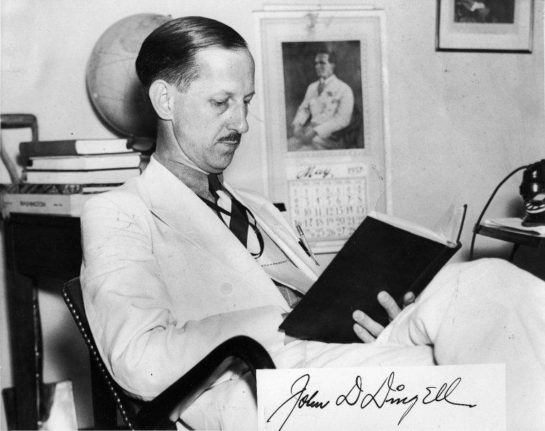 Representative John D. Dingell (D-MI) reading a book in his office