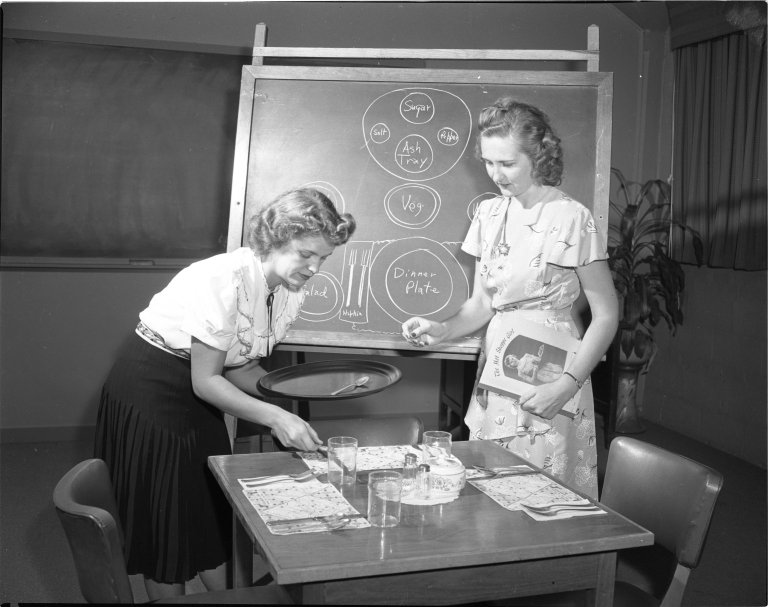 Two female employees of Hot Shoppes, a food service company founded by J. Willard Marriot, practice place settings