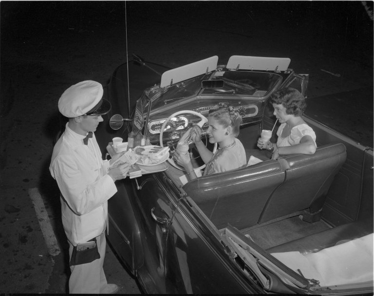 A waiter brings an order out to his customer's car