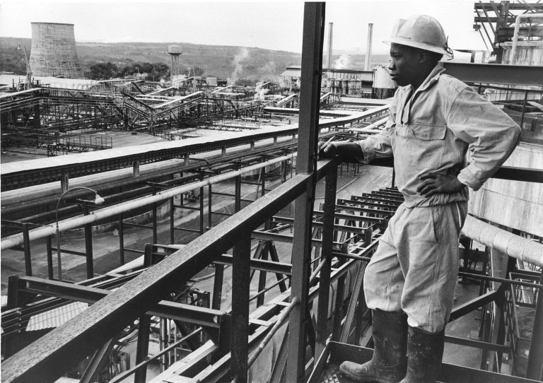 An African worker looks out across the Fria Company International for the Production of Aluminum facility