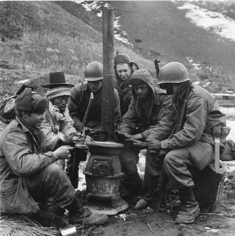 American soldiers and a Korean man huddling around a stove to keep warm