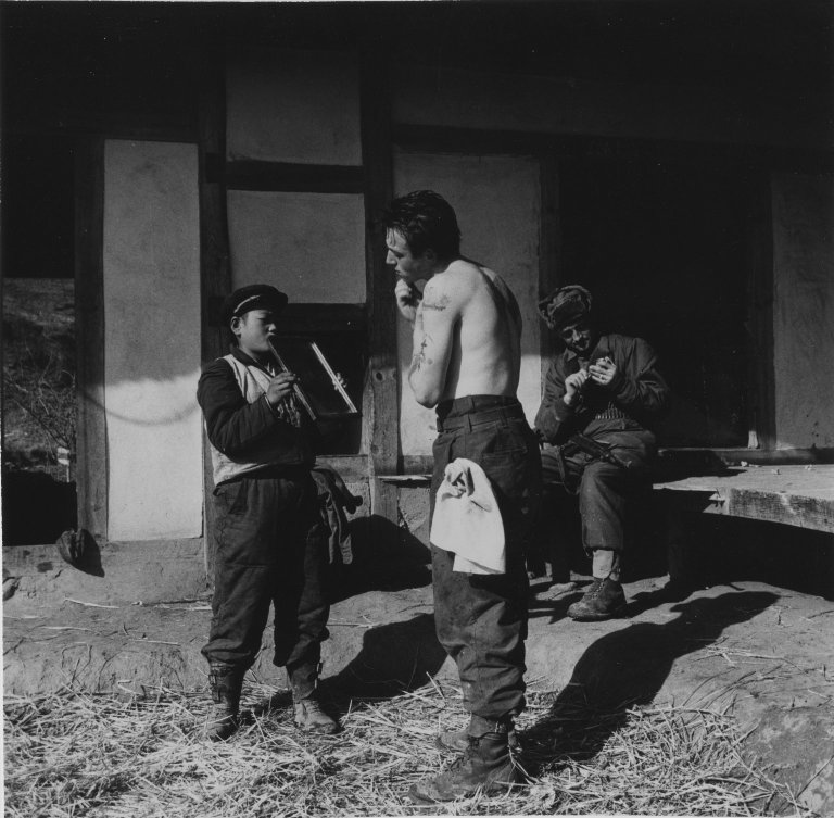 Korean boy holding a mirror for shaving French soldier.