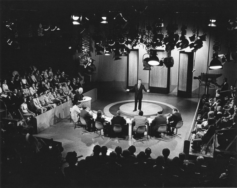 President Nixon speaking in front of a panel in a television studio