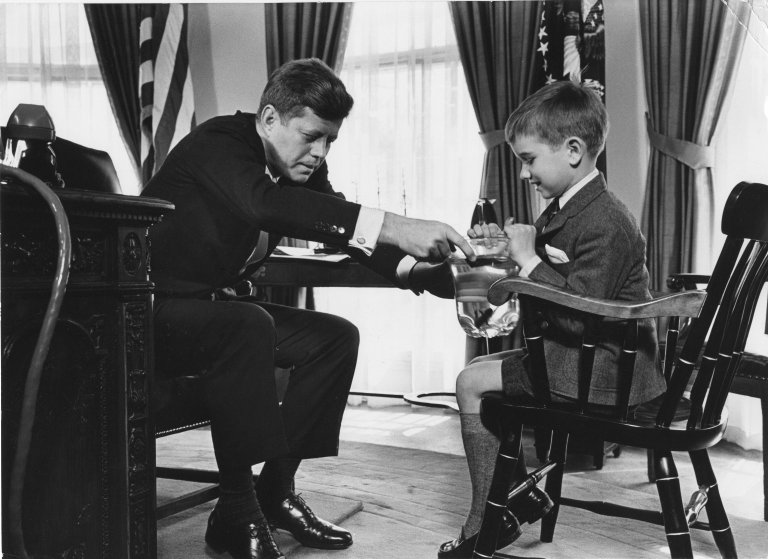 President Kennedy's nephew, Robert, brings him a salamander in the Oval office