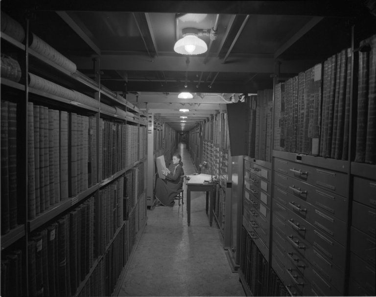 Employee of the National Archives sitting in a long hall way filled with documents