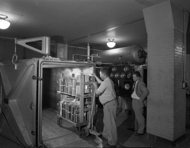 Employees of the National Archives loading a cart of books into a large machine