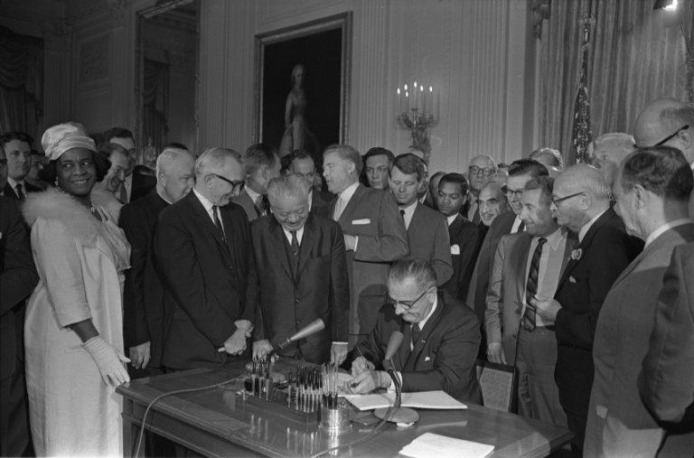 President Johnson, surrounded by supporters and legislators, signing the Civil Rights Act of 1964