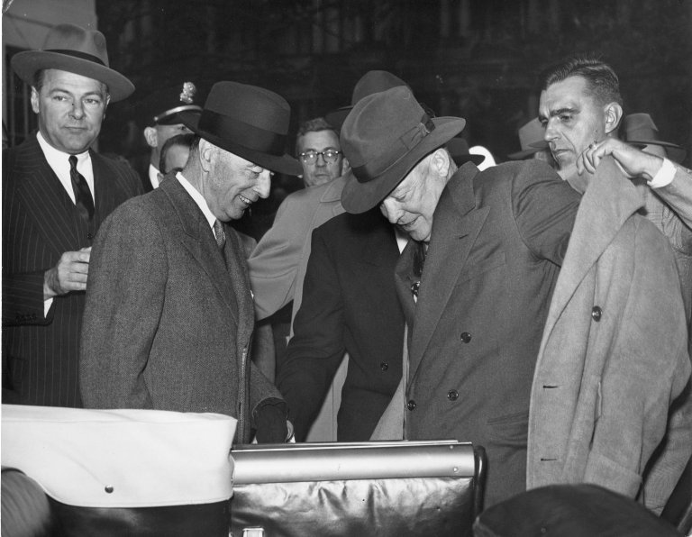 An aide helps President-Elect Eisenhower put on his coat