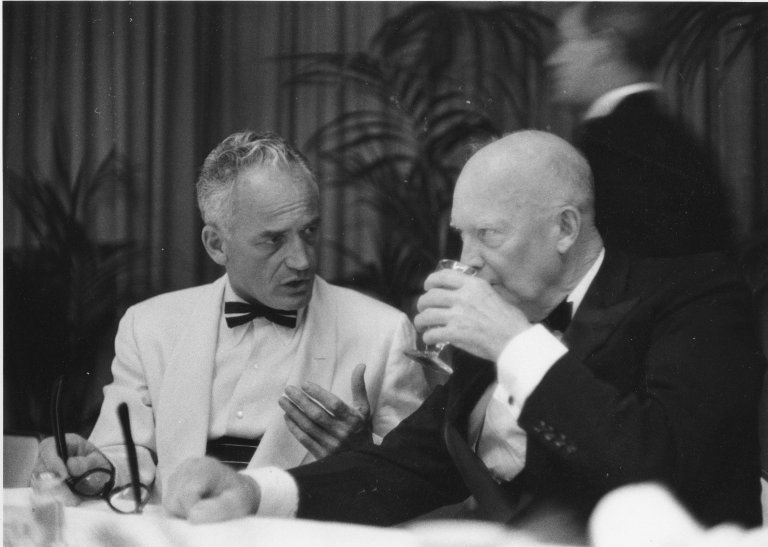 President Eisenhower takes a drink while talking with an unidentified man