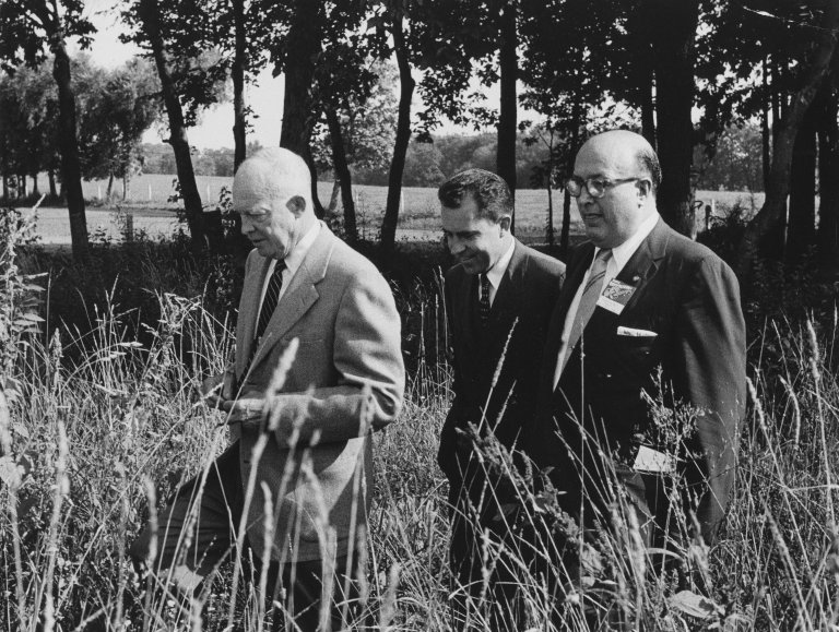 President Eisenhower, Vice President Nixon and an unidentified man walk through a field