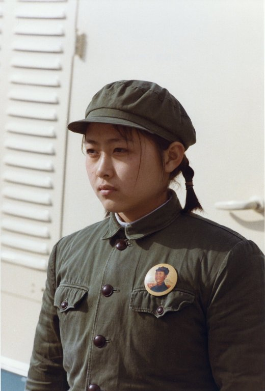 A Chinese woman wearing a uniform and a large button