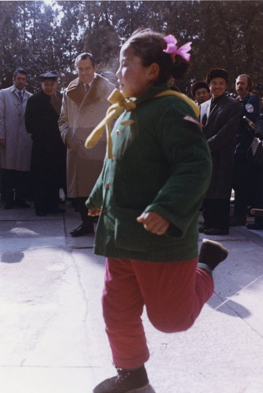 President Nixon and others watch a young Chinese girl dance