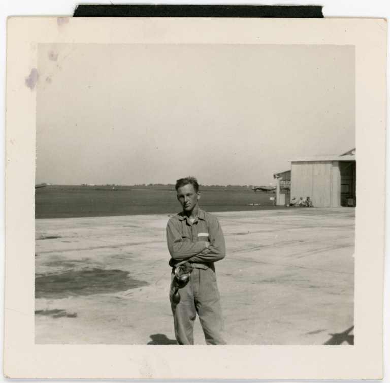 Daniel Monson standing in front of an air field, likely Kelly Field in San Antonio, Texas.