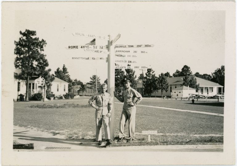 Daniel Monson standing with his brother Roy Monson in front of a directional sign.