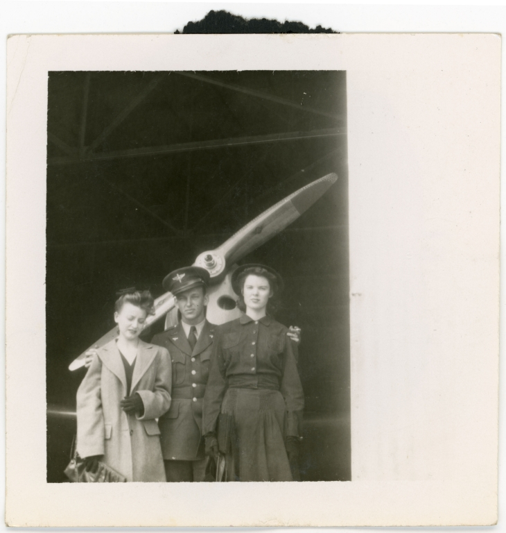 Daniel Monson standing with two women in front of a plane.