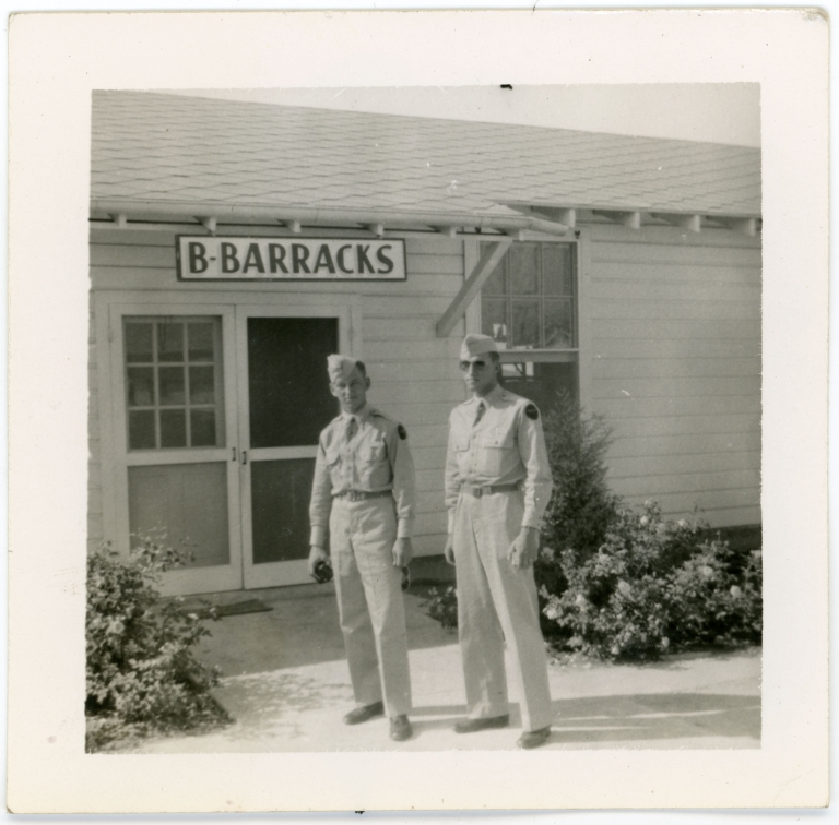 Daniel Monson standing with a man in front of B Barracks, likely at Kelly Field.