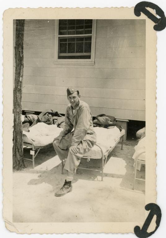 Daniel Monson sitting on a cot outside in uniform.