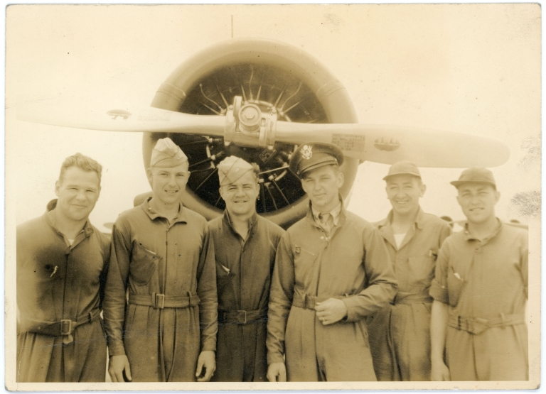 Daniel Monson standing with other officers in front of a plane.